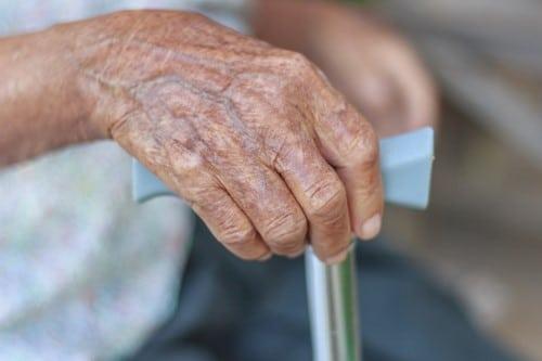 Oude hand met kruk